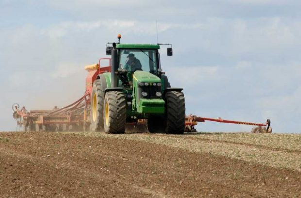 Image of a green tractor plowing a field.