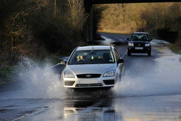 Image of a car driving through a flood.