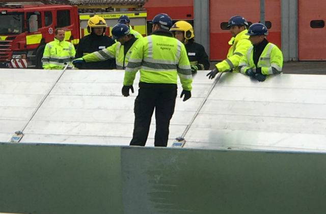 Environment Agency workers putting up flood barriers