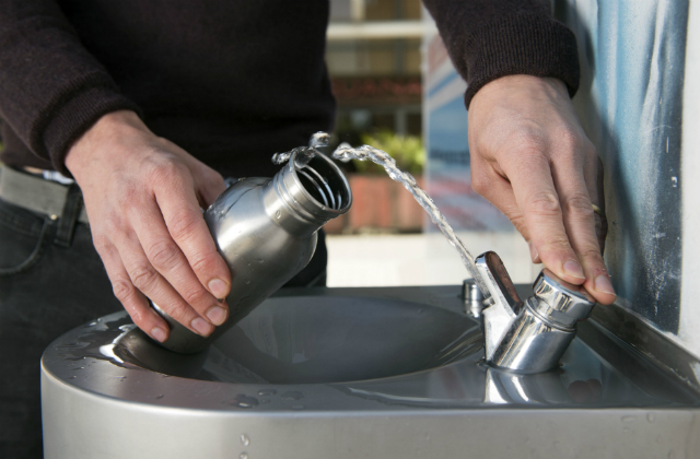 Image shows a person filling up a drinks bottle with water