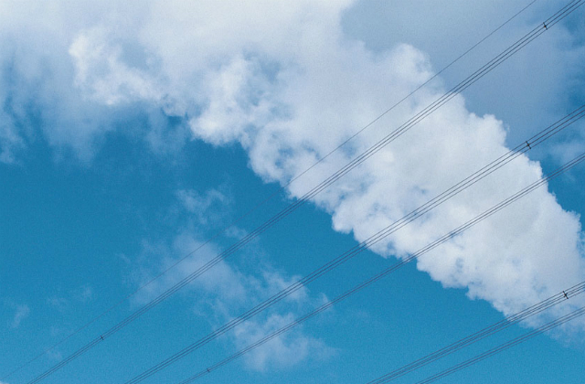 An image of telephone lines against clouds and a blue sky.
