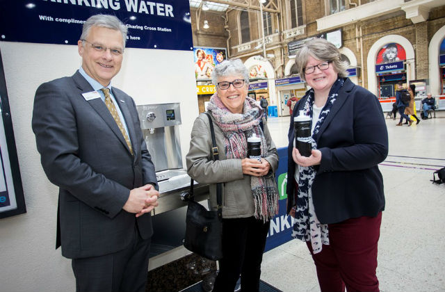 Photo of 3 people stood by a free water drinking fountain in Charing Cross station.