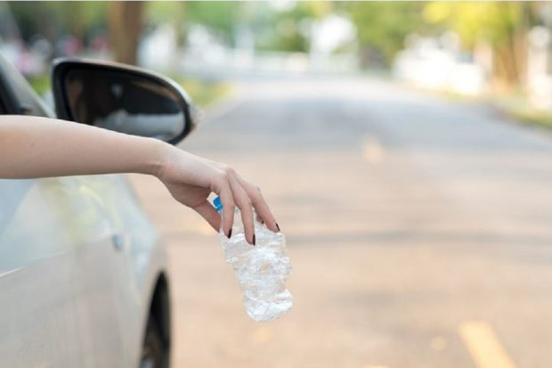 Photo of a woman's hand dropping a used plastic bottle out of a car window