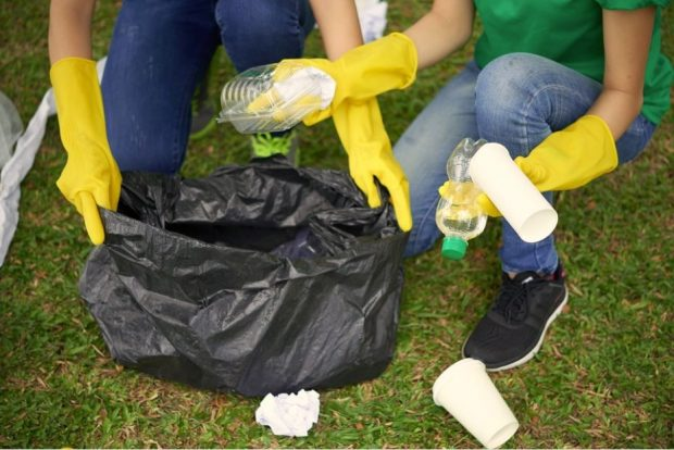 A close up image of two people collecting litter.