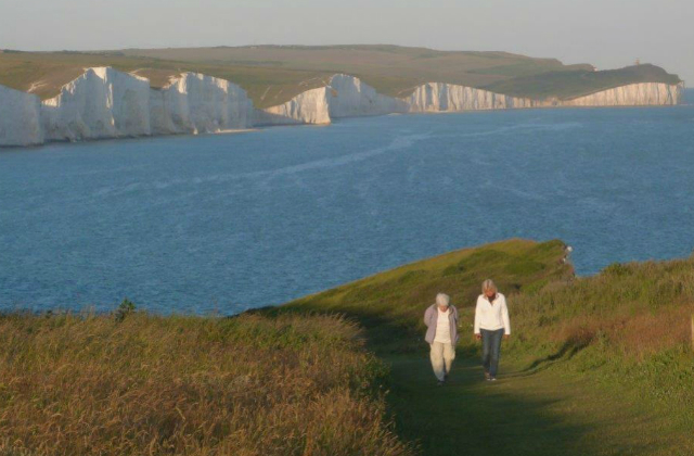 Two people walking on a coastal path against a backdrop of white cliffs and the sea.