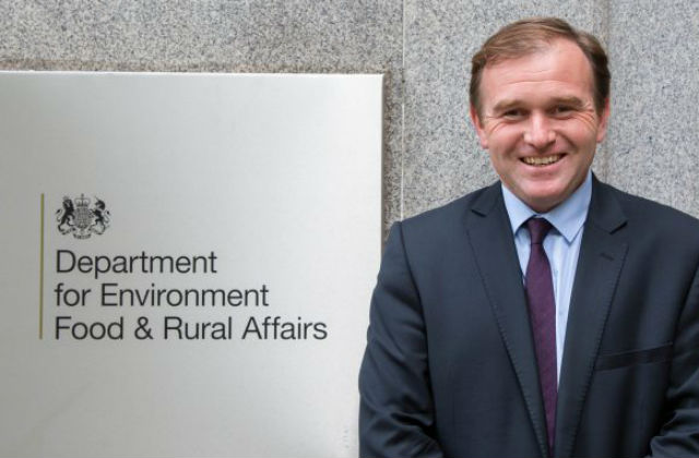 Minister Eustice standing against a sign which says 'Department for Environmnet Food and Rural Affairs'.