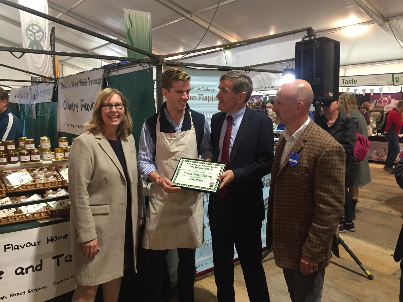 An image of Defra Minister David Rutley meeting farmers and food producers at Westmorland Show. He is holding a 'first place' sign.