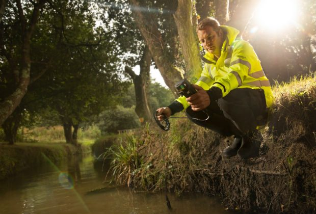 An image of a man kneeling by a river wearing a high vis yellow jacket.