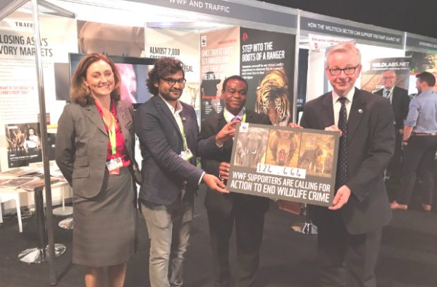 An image of Environment Secretary Michael Gove accepting a petition from the WWF, standing surrounded by three other people.