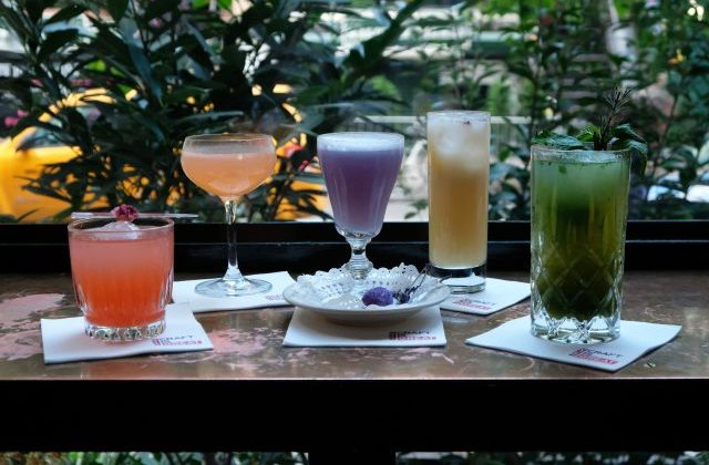Different coloured cocktails on a wood table.