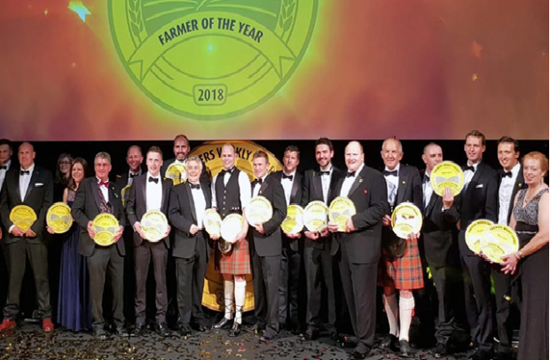 Image of winners standing holding their prizes at the Farmers Weekly Awards.