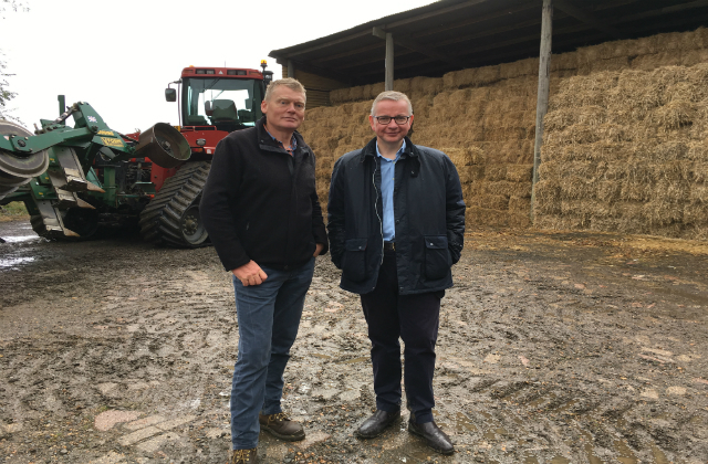 An image of the Secretary of State at a farm with Countryfile presenter Tom Heap.