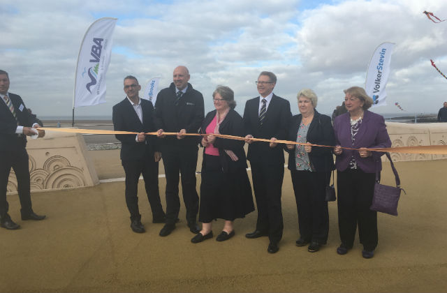 Image of Minister Coffey at the flood defence opening cutting the ribbon surrounded by 5 other people.