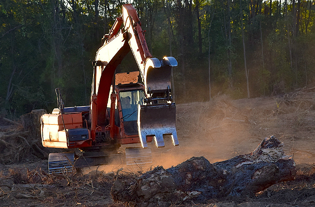 An image of a  bulldozer in the process of removing soil from the ground.