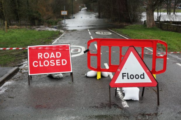 Image of a road closed sign and a flood sign against the backdrop of a road.