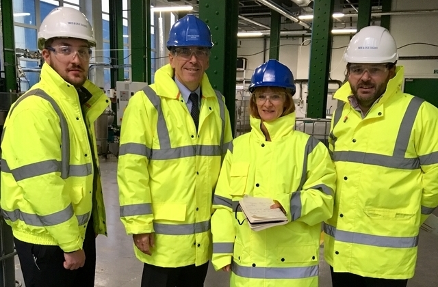 Minister Rutley in a high vis jacket and a helmet standing at the Tate and Lyle factory surrounded by three other people.