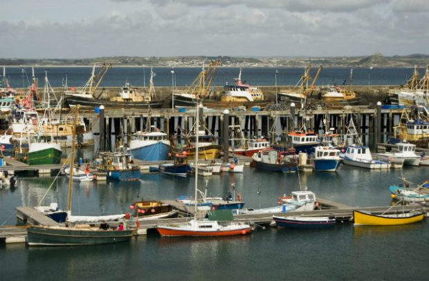 An image of fishing boats in a harbour against a grey sky.
