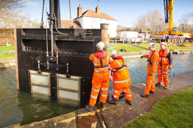 Four operational EA officers working on Thames improvements next to the river.