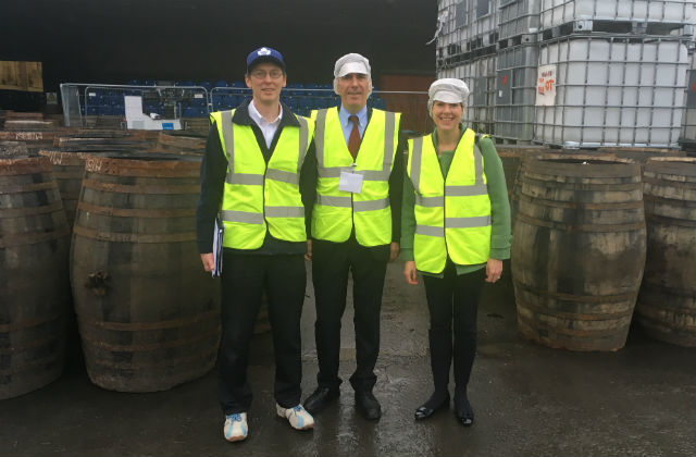 An image of Minister Rutley standing at a liquor factory wearing a high vis vest surrounded by two other people.