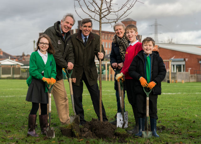Minister Rutley standing in a field planting a tree with Tree Champion Sir William Worsley and pupils from St Andrew's CE Primary School. Photo credit: The Woodland Trust.