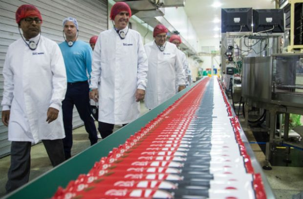 Minister Rutley and several other people walking past a supply chain conveyor belt at the Nestle factory.