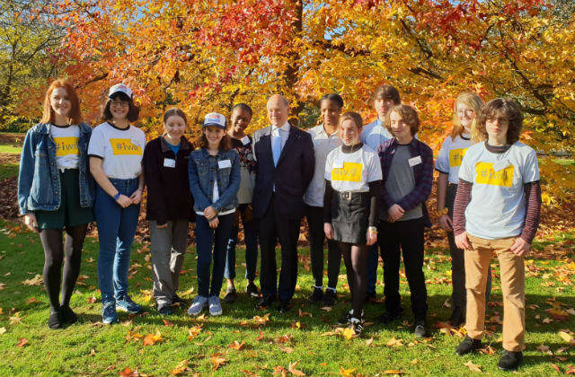 Lord Gardiner standing against a wooded backdrop surrounded by young environment ambassadors.