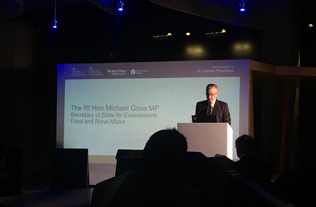 An image of nvironment Secretary Michael Gove speaking on stage at the launch of the UKCCP. The presentation behind him says 'The Rt Hon Michael Gove MP, Secretary of State for Enviroment, Food and Rural Affairs'.