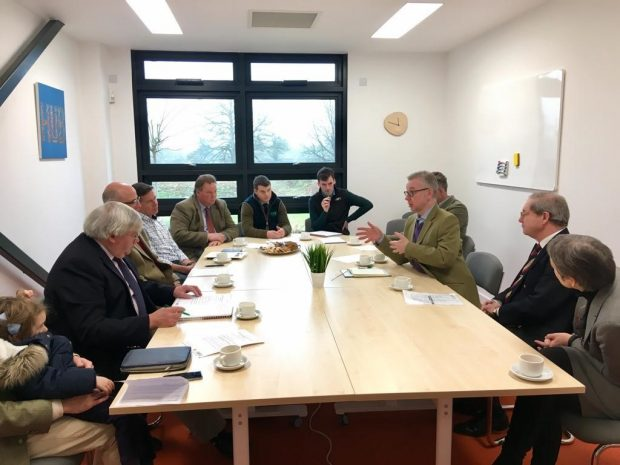 The Environment Secretary speaking at a roundtable with the Royal Agricultural University and Gloucestershire Wildlife Trust, surrounded by other people.