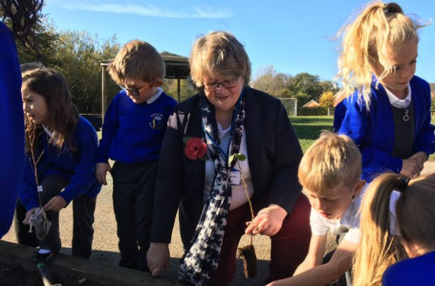 An image of Minister Coffey kneeling next to pupils from Saxmundham Primary School