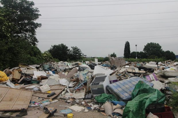 Image of waste in a dump against a gray sky.