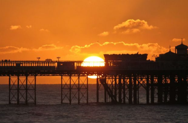 Image of a sunset behind a pier on a beach