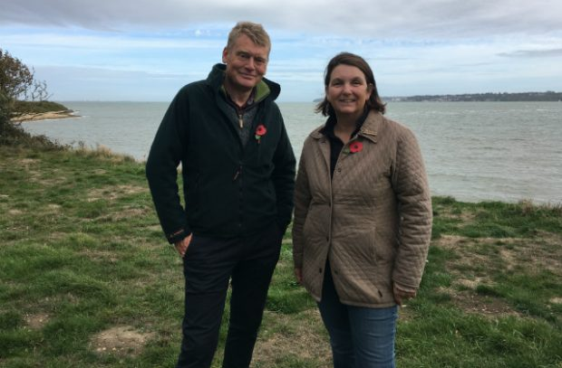 Nicola Spence and Tom Heap stand in a field against a body of water.