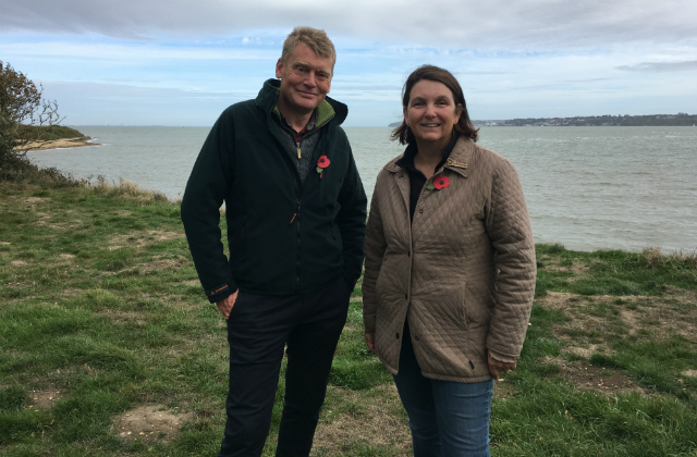An image of Nicola Spence and Tom Heap standing in a field against a body of water.