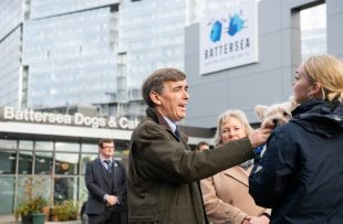 An image of Minister Rutley speaking to a group of people outside Battersea Dogs and Cats Home.