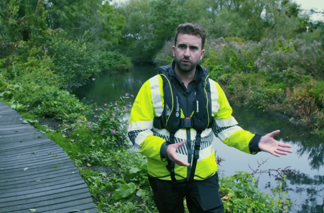 An image of Environment Agency officer Mathew Reed explaining his work investigating Symphony Chauffeurs, standing next to a body of water wearing a high vis jacket.