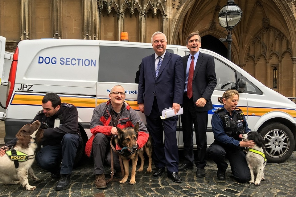 Image of PC Wardell, Sir Oliver Heald and Animal Welfare Minister standing in front of a van with dogs.