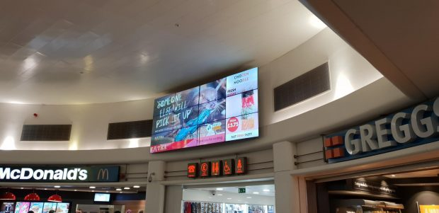 Image of a service station with anti-litter campaign advert on the screen.