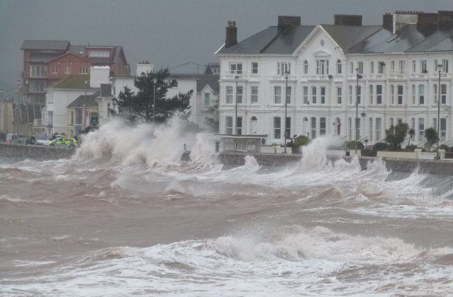 An image of high seas coming up against the Exmouth harbour.