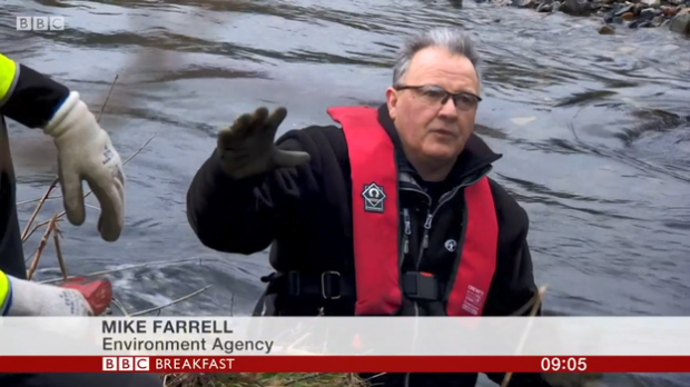 An image of Mike Farrell from the Environment Agency speaking on BBC Breakfast wearing a red vest against a backdrop of water