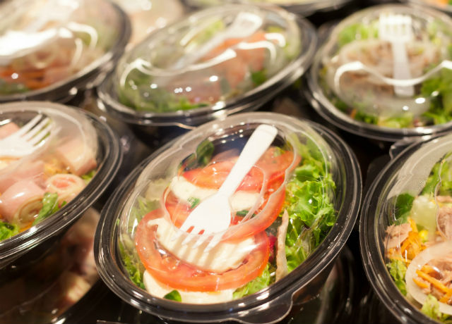 An image of various salads in takeout containers.