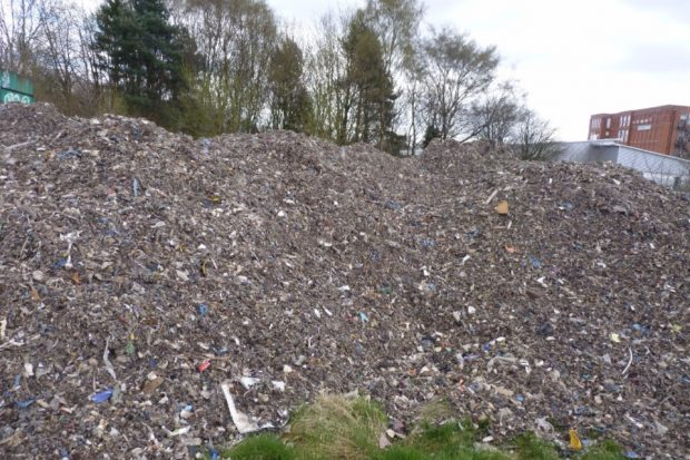 Image of 100 tonnes of waste outside a school