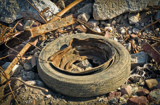 Image of a rusty old tyre amongst rubble.