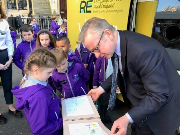 Image of Michael Gove looking at primary school children's workbook.
