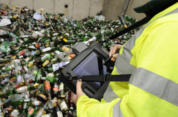 Image of a woman with a screen looking at a pile of glass bottles.
