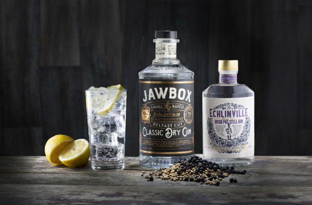 An image of a glass of gin and tonic on a table next to two bottles of Gin labelled Jawbox and Echlinville.