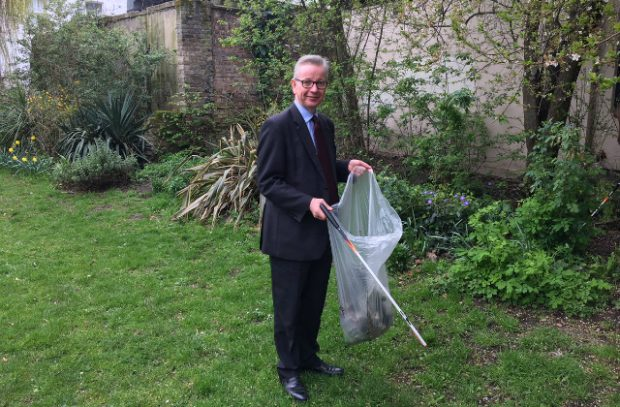 Image of Environment Secretary holding a rubbish bag collecting litter