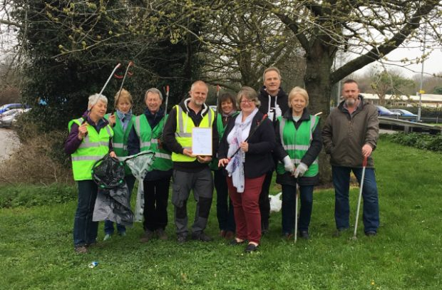 Minister Coffey (centre) with a group of people holding litter-pickers and bin bags on grass