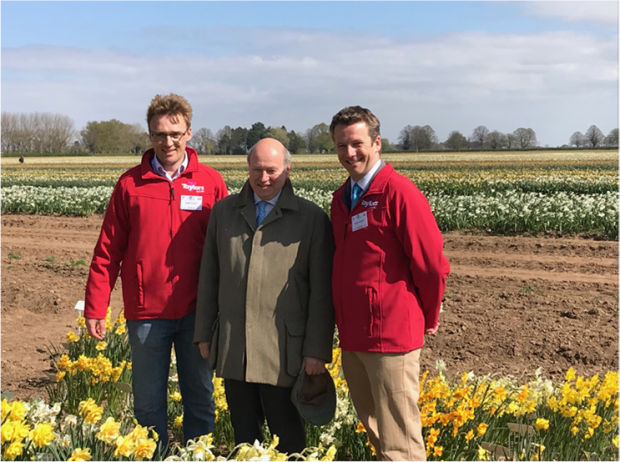 Lord Gardiner and two men in red jackets standing in front of daffodil field