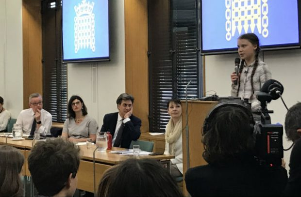 • Picture of Greta Thunberg speaking behind a podium and a panel comprised of Environment Secretary Michael Gove, and MPs Layla Moran, Ed Miliband and Caroline Lucas.