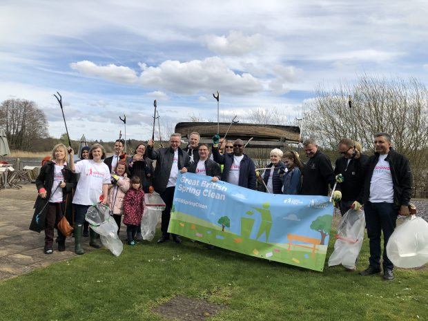 Image of Environment Secretary and a group of people holding a banner which says 'great british spring clean'